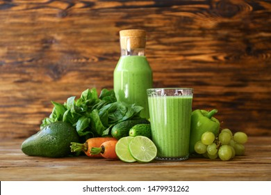 Tasty green smoothie with ingredients on wooden table