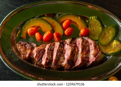 Tasty grilled beef barbecue steak Machete with vegetables, spices and herbs on wooden table.