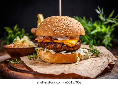 Tasty grilled beef burger with cheese and cabbage served on pieces of brown paper