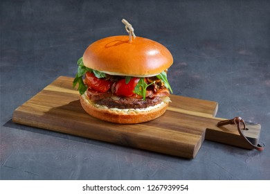 Tasty grilled beef burger with lettuce, cheese and onion served on cutting board with copyspace