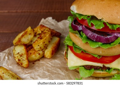 Tasty grilled beef burger with lettuce and potatoes on paper and wooden background. Big hamburger for lunch. Food photo.
