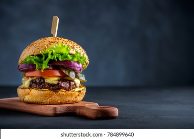 Tasty grilled beef burger with lettuce, cheese and onion served on cutting board on a black wooden table, with copyspace