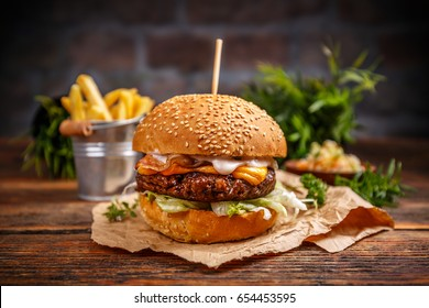 Tasty grilled beef burger served on pieces of brown paper on a rustic wooden table