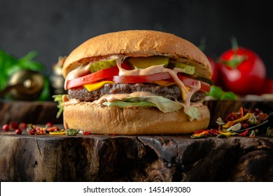 Tasty grilled burger with with beef, cheese, vegetables.  Delicious grilled Cheeseburger on a dark background. Free space for text