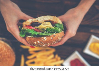 Tasty grilled burger, french fries and ketchup. Fast food, people and eating concept. Close up of hands with burger. French fries into ketchup bowl on wooden table. Selective focus.