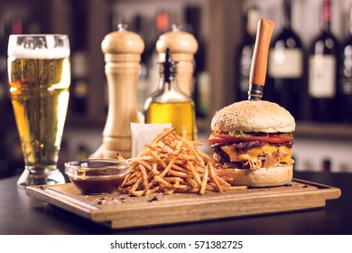 Tasty grilled cheeseburger with a knife stabbed trough on a wooden plate. Burger with pickles, cheese, tomatoes and french fries on the side. Napkins and beer on the side. Olive oil in the background.