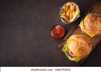 Tasty grilled home made burger with beef, tomato, cheese, cucumber and lettuce on a dark stone background with copy space. Top view. fast food and junk food concept
