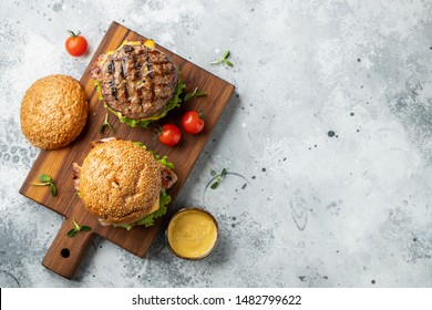 Tasty grilled home made burger with beef, tomato, cheese, bacon and lettuce on a light stone background with copy space. Top view. fast food and junk food concept. Flat lay