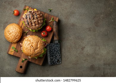 Tasty grilled home made burger with beef, tomato, cheese, bacon and lettuce on a dark stone background with copy space. Top view. fast food and junk food concept. Flat lay