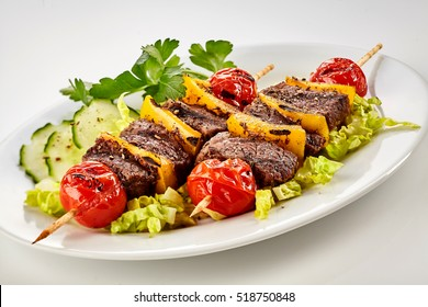 Tasty grilled marinated beef shish kebabs with colorful bell pepper and tomato on wooden sticks served on a bed of fresh salad with cucumber and coriander