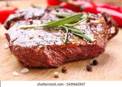 Tasty grilled meat on wooden board, closeup