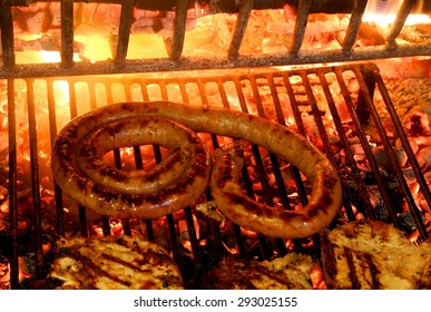 tasty grilled meat with sausage and pork chop in the fireplace with the glowing embers