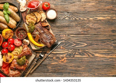 Tasty grilled meat with sausages and vegetables on wooden background
