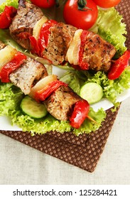 tasty grilled meat and vegetables on skewer on plate, on table