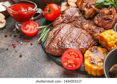 Tasty grilled meat with vegetables on table