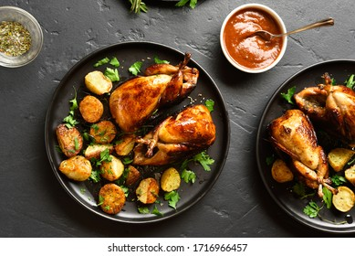 Tasty grilled quails carcasses on black stone background. Roasted quails on plate. Top view, flat lay