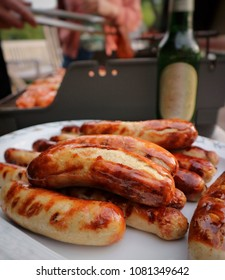 Tasty grilled sausages on a plate and bottle of beer on a background. People enjoying grilling outdoors. Grilled food concept. Close up.