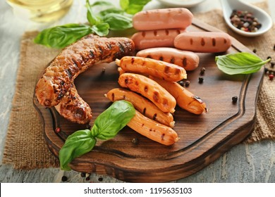 Tasty grilled sausages on wooden board