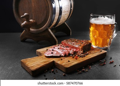 Tasty grilled steak with beer on cutting board