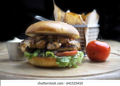 Tasty grilled  tenderloin beef burger with cheese and mayonnaise tomato served on a wooden plate wooden of counter, with darken background