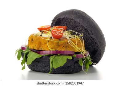 Tasty grilled veggie burger with chickpeas and vegetables on black bread on white background.