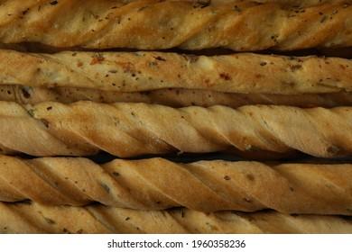 Tasty grissini breadsticks on whole background, close up
