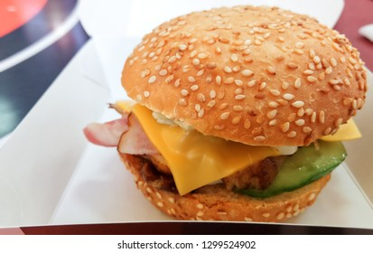 Tasty hamburger. Fast food restraint. Non healthy food. Cheese and bacon.