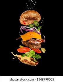 Tasty hamburger with flying ingredients on dark background. High resolution image.