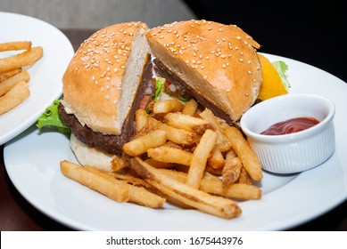 Tasty hamburger with lettuce and tomato cheese, served on white plate on table, restaurant interior and container with tomato sauce.