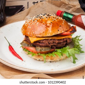 Tasty hamburger with meat, fresh green, cheese, and pepper on the plate with a cruft paper
