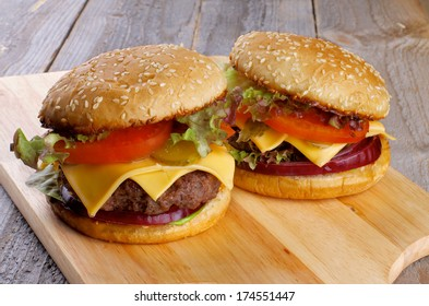 Tasty Hamburgers with Beef, Tomato, Lettuce, Pickle, Red Onion and Cheese into Sesame Buns closeup on Wooden Cutting Board