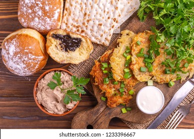 Tasty Hanukkah celebration food: homemade traditional potato, crunchy matzo, liver pate, sweet donuts on vintage cutting board. Rustic wooden background. Top view