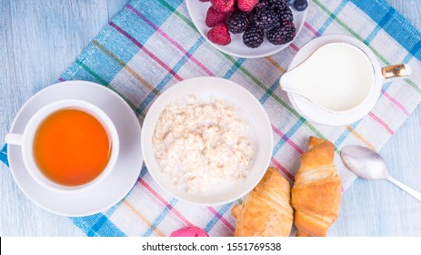 Tasty and healthy breakfast - bowl with oatmeal with raspberries, blueberries and blackberries, a cup of green tea, milk jug and croissants