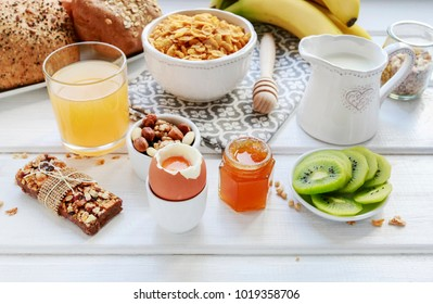 Tasty and healthy breakfast. Variety of food on white wooden kitchen table. Milk, honey, corn flakes, sliced fruits and muesli bars.