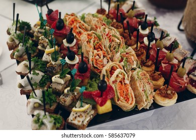 Tasty healthy canape snacks close-up, olives with cheese and meat, lemons with fish food at wedding reception, restaurant catering concept
