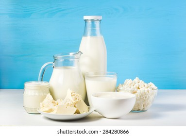tasty healthy dairy products on a table on a blue background: sour cream in a white bowl, cottage cheese in bowl, cream in a a bank,  butter on a saucer and milk in a jar, glass bottle and in a glass