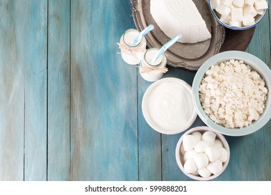tasty healthy dairy products on a table on a blue background: sour cream, cottage cheese, mozzarella cheese, butter,ricotta and milk in a bottle