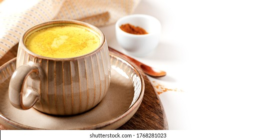 Tasty healthy drink made from turmeric, milk and spices in a mug on a white background, free space for text. Golden milk. Latte made from milk and turmeric. Detox drink.