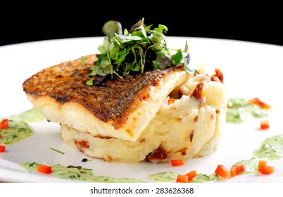 Tasty healthy fish fillet with potato puree with dried tomatoes and wild garlic sauce