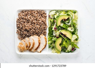Tasty healthy food. Boiled buckwheat with grilled chicken amnd fresh green salad on rectangle plate. Loosing weight concept.