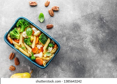 Tasty healthy lunch to go with pasta and vegetables, fruits and nuts on grey background. Healthy eating, school, food to go concept.