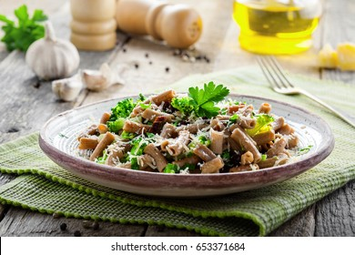 Tasty healthy meal made of rye pasta, broccoli, cheese and parsley on a table. Healthy fiber lite low-fat food on a rustic table.
