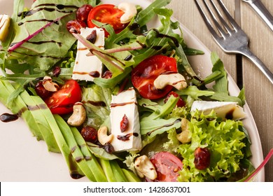 Tasty and healthy salad with arugula, brie, cheese, avocado, cherry tomatoes, dry cranberry and cashews. Top view. The flat lay. Banner