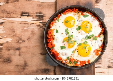 Tasty and Healthy Shakshuka in a Frying Pan. Fried eggs with tomatoes, bell pepper, vegetables and herbs. Middle eastern traditional dish