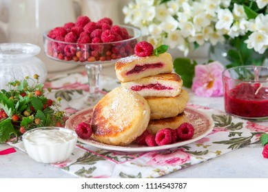 Tasty healthy summer breakfast concept. Cottage cheese pancakes syrniki with raspberries