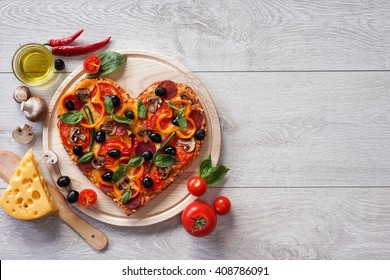 Tasty heart shaped pizza decorated with vegetables and herbs on white wooden background. High resolution product.