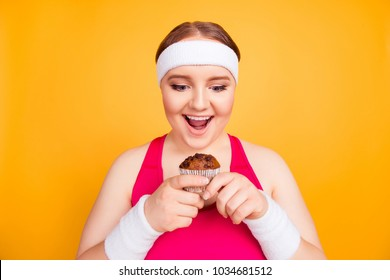 So tasty, high-calorie, tempting! Funny excited cheerful fatty woman wearing sweat-band is holding a chocolate cupcake, looking with open mouth, she can put on weight, isolated on yellow background