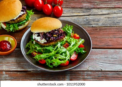 Tasty home made meat burgers with fried onion, tomato sauce and lettuce in classic buns on plate over old wooden table background. Side view, copy space. Rustic style. Homemade fast food.