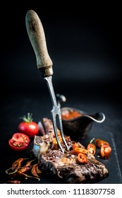 Tasty homemade beef grilled steak served with meat fork, tomatoes, chili pepper and pot of sauce on dark cooking board