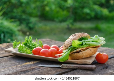 Tasty homemade burger with meat, lettuce, tomatoes, sesame bun on picnic table in garden outdoors.